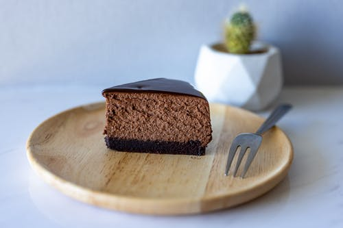 Slice of Chocolate Cake on Round Wooden Tray