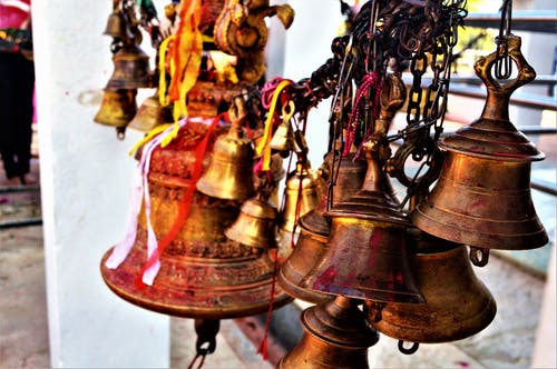 Hanged Brown Metal Bell in Close Up Photography