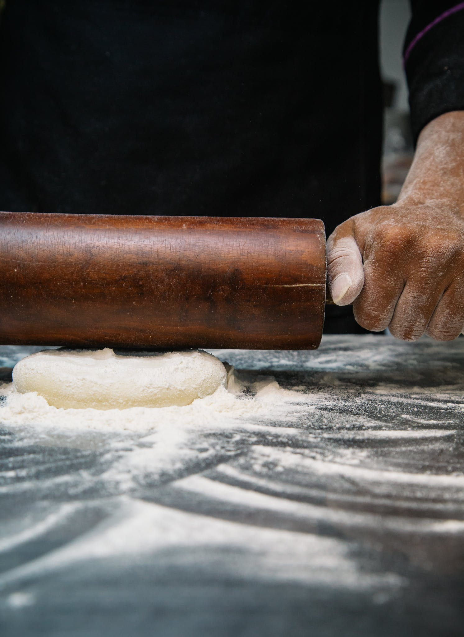 Person Using Brown Wooden Rolling Pin