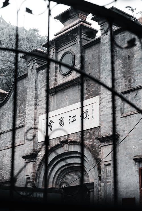 Old building with sign inscription and metal gate