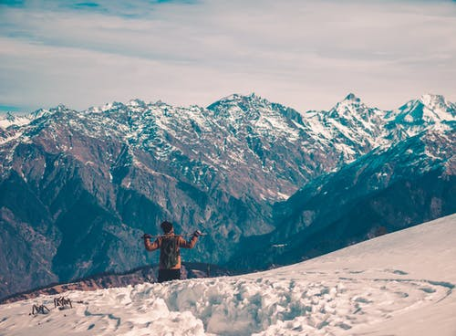 Person in Black Jacket Standing on Snow Covered Mountain