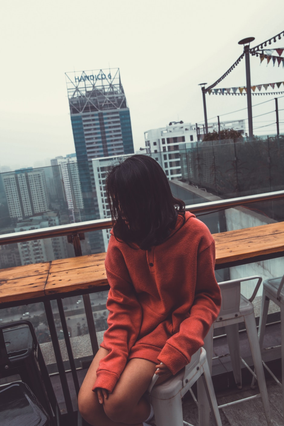 Photograph of Woman Wearing Red Pullover Hoodie Jacket Sitting on White Barstool