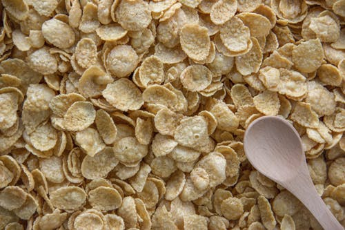 Bunch of Brown Crunchy Cereals with Wooden Spoon