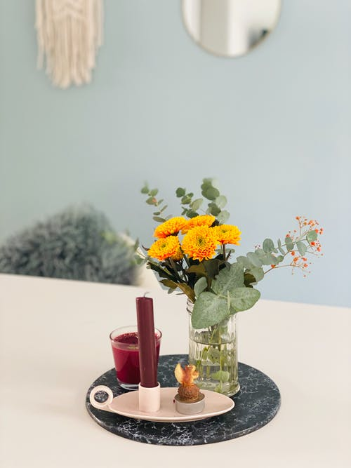 Yellow and White Flowers in Clear Glass Vase on Table