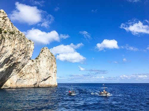 People Riding on Boat on Sea Near Brown Rock Formation Under Blue and White Cloudy Sky