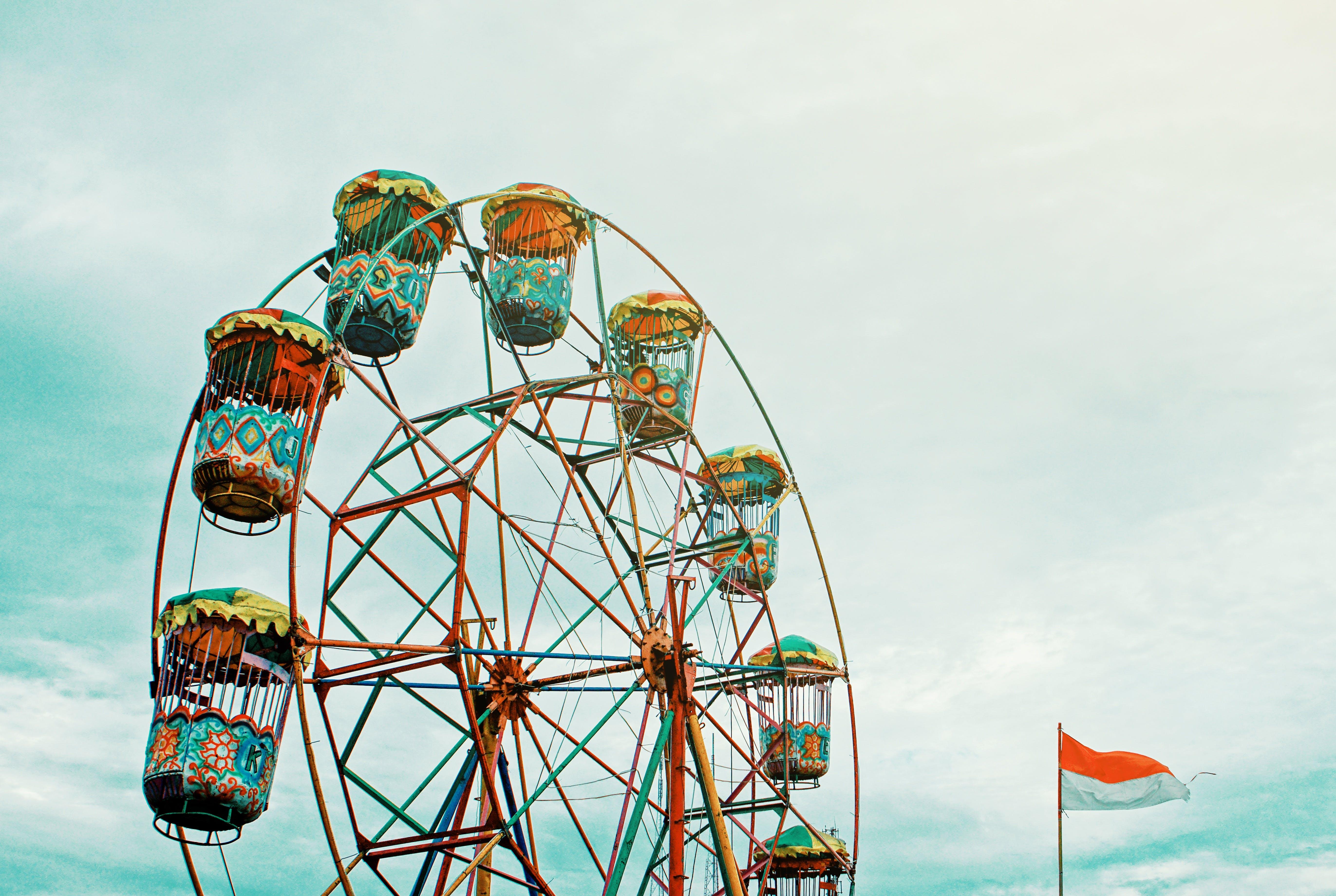 Photography of Orange Ferris Wheel Beside White and Orange Flag