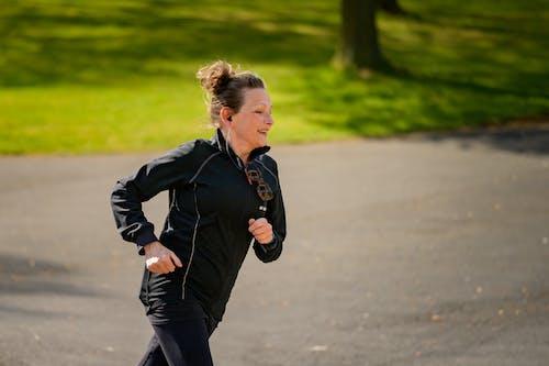 Woman in Active Wear Jogging on Gray Asphalt Road