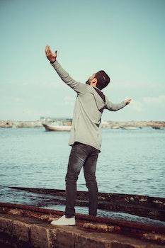 Man In GrEy Hoodie Standing on Grey Pavement Near Sea
