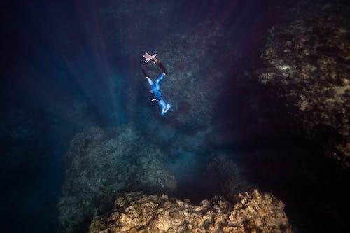 Unrecognizable diver swimming in sea water