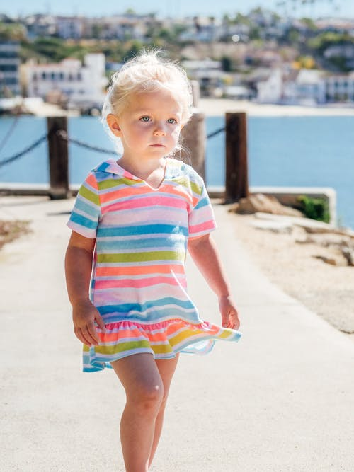 Girl in White Green and Pink Striped Dress Standing on Brown Sand Near Body of Water