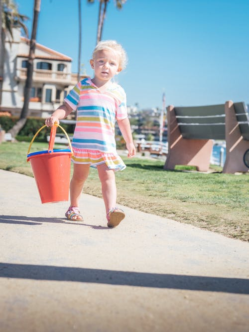 Girl in White and Pink Stripe Shirt Holding Red Plastic Bucket