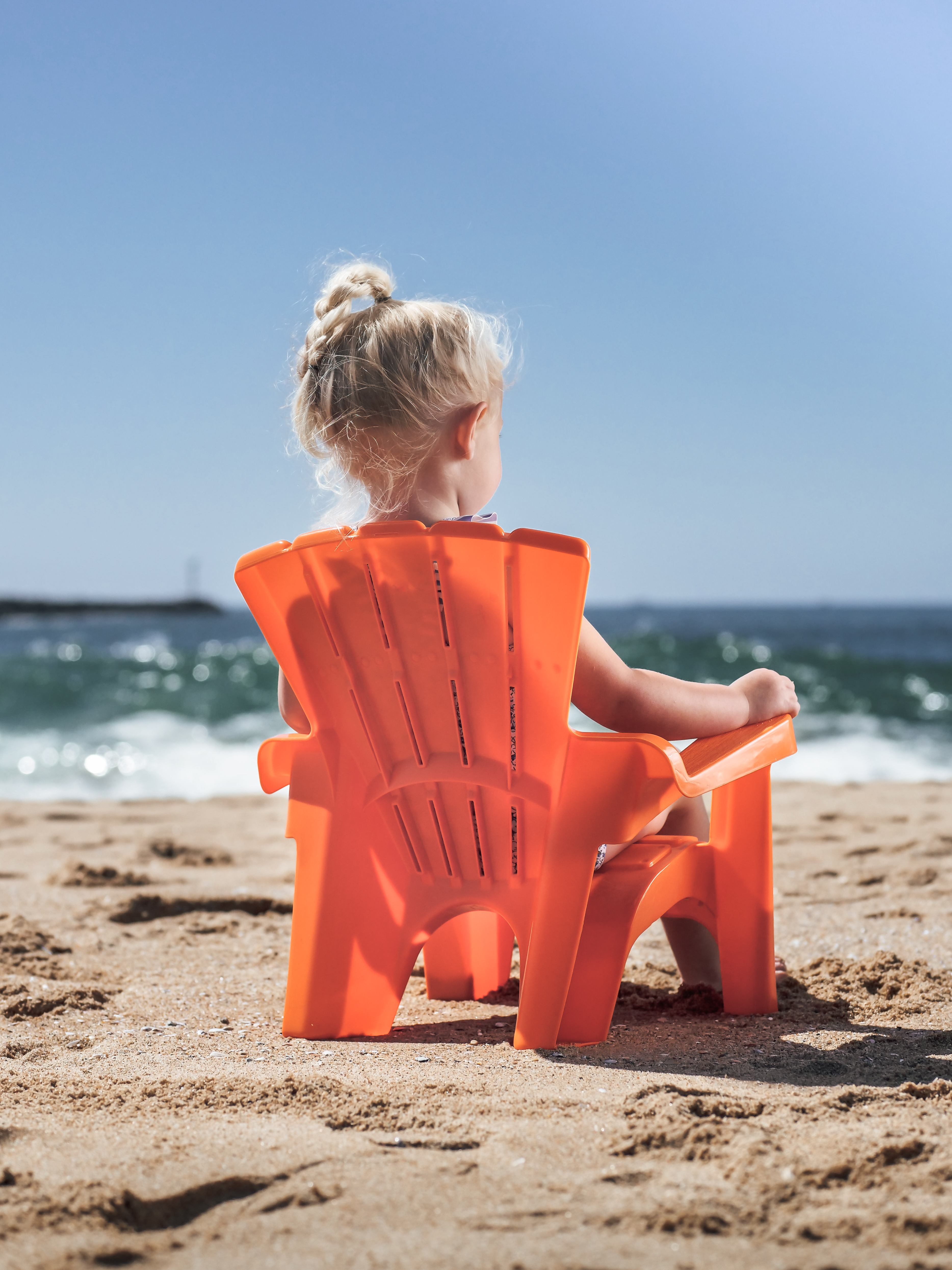 girl sitting on red plastic chair on beach