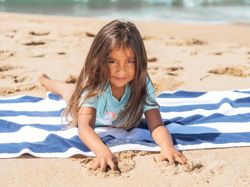 Girl in Blue Shirt Sitting on White and Blue Stripe Textile on Beach