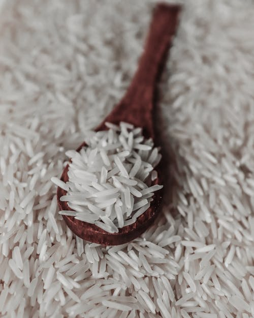 From above of raw white rice grains on wooden spoon placed on pile