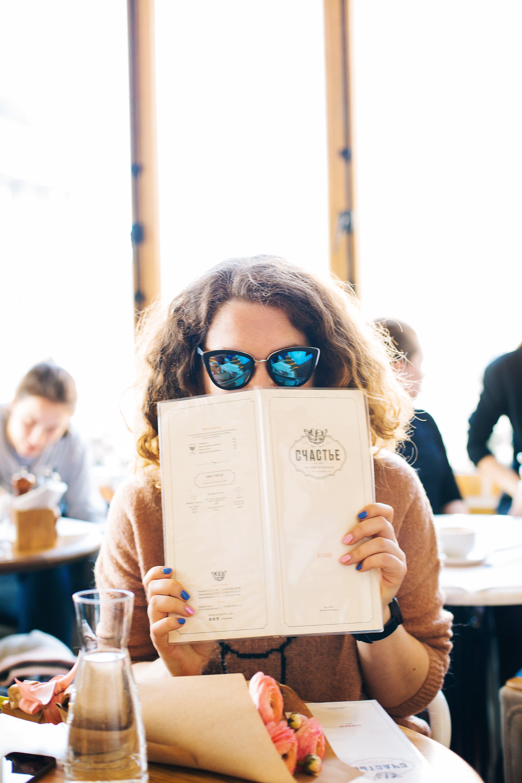 Woman in Black Sunglasses Holding Menu