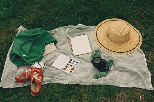 Black Dslr Camera on White and Red Book Beside Brown Fedora Hat and Red and White