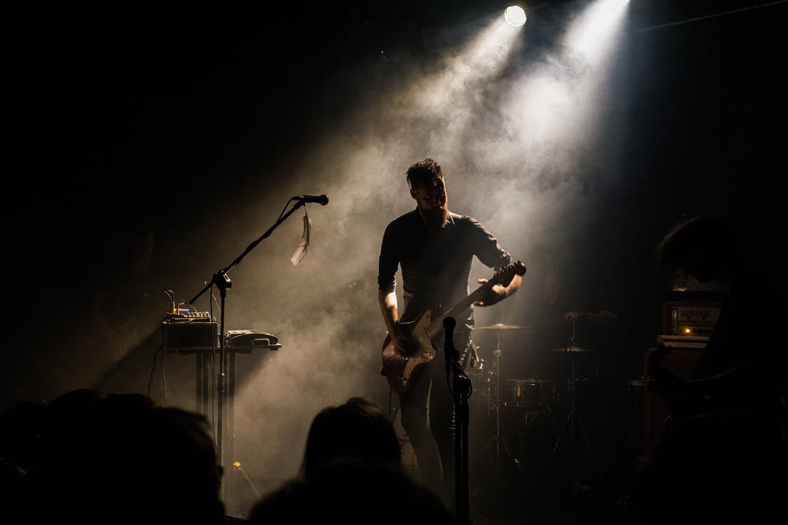 Man Playing Guitar in Front of People