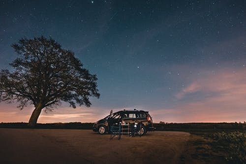 Black Suv on Brown Field during Night Time