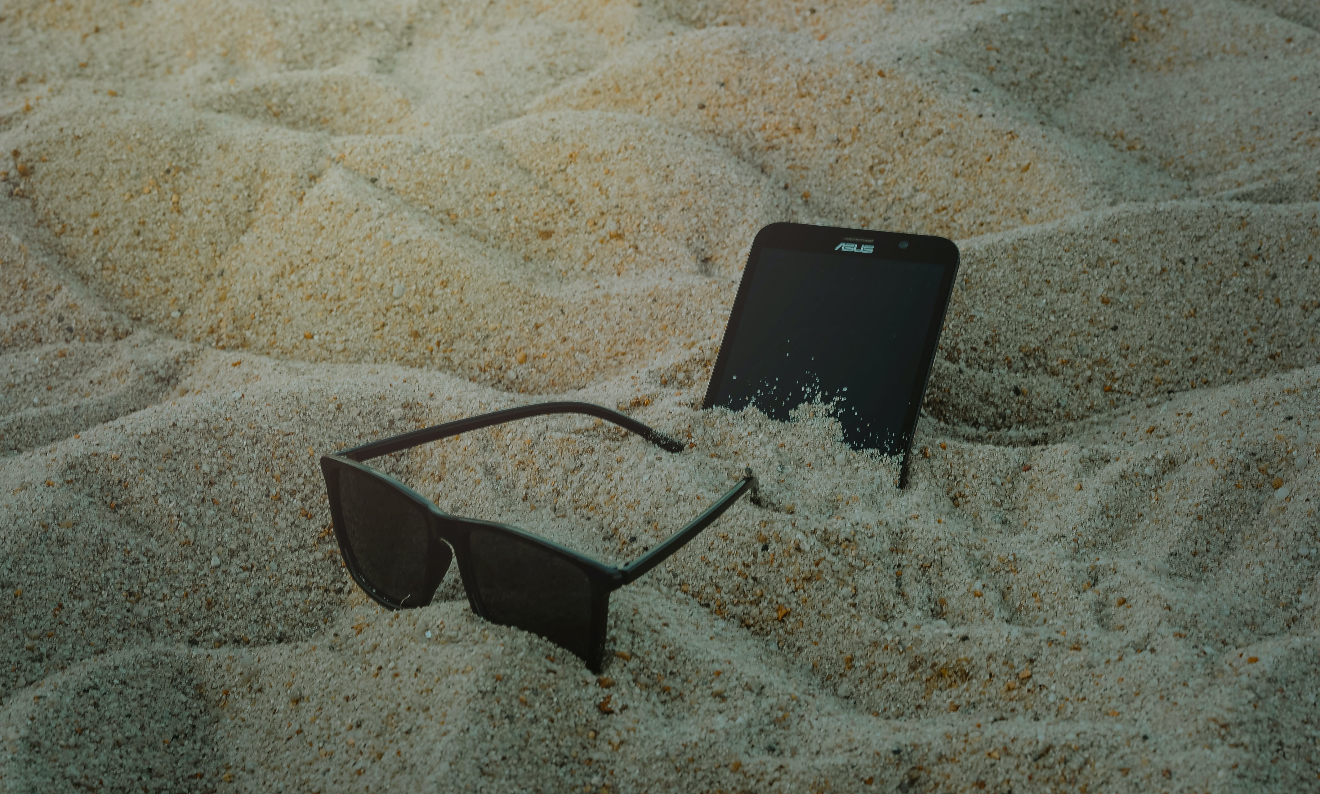 Photo of Phone and Sunglasses on Sand