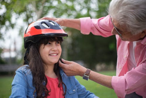 Woman in Blue Shirt Wearing Red and Black Helmet