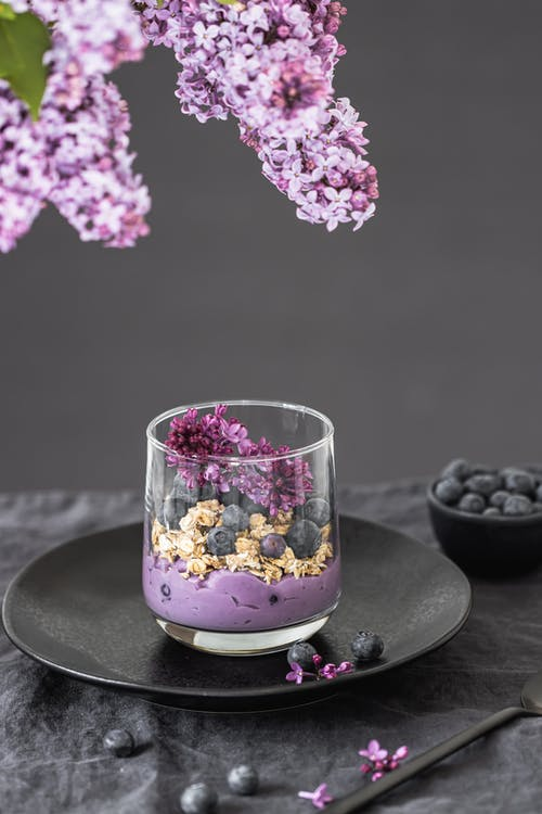 Clear Drinking Glass With Pink Flowers on Black Round Plate