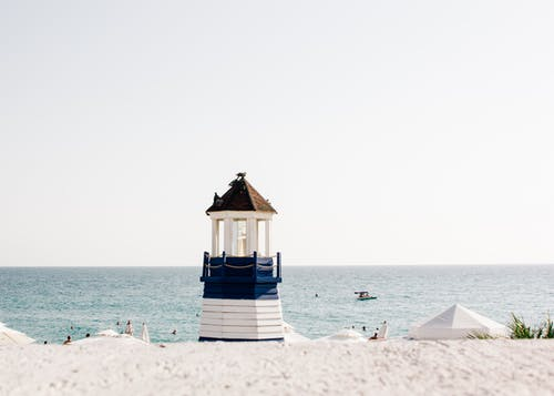Photo of Blue and White Painted Lighthouse Near the Beach