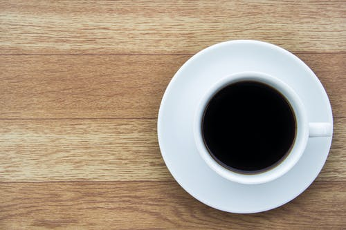 Close-Up Shot of a Cup of Coffee on a Wooden Surface