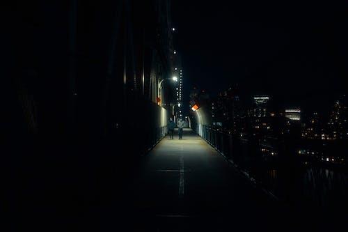 People Walking on Sidewalk during Night Time