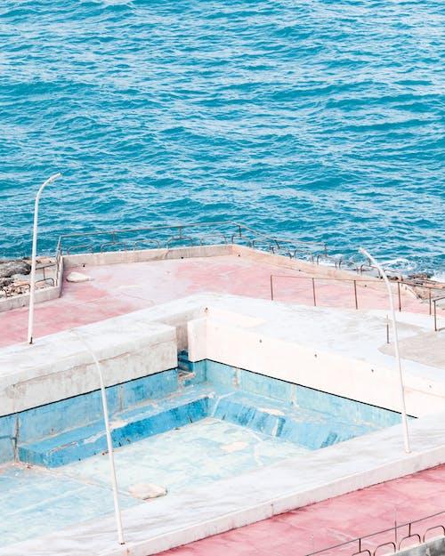 Brown Concrete Swimming Pool Beside Blue Sea