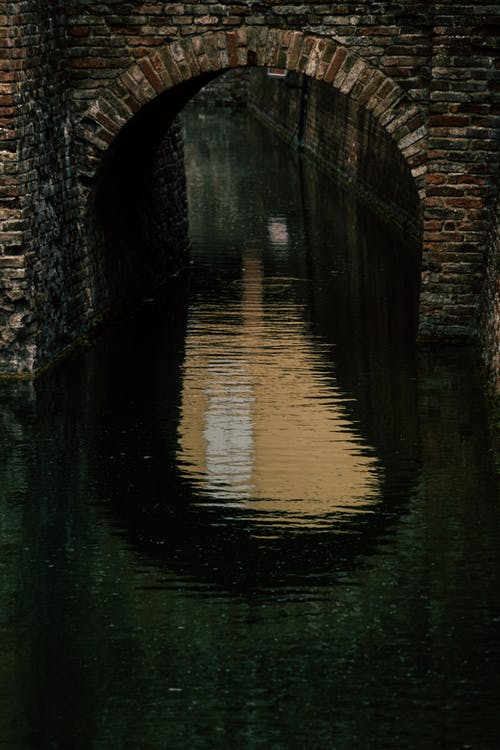 Reflection of Gray Concrete Bridge on Water
