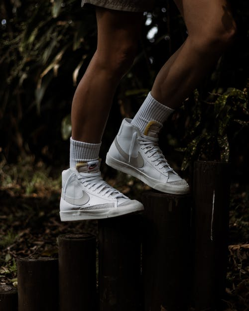 A Person Wearing White Nike Sneakers