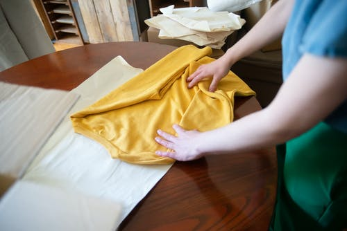 A Person Folding a Yellow Shirt on a Wooden table