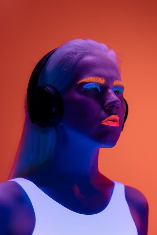 Woman with Neon Make Up Wearing Black Headphones