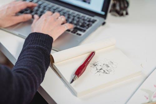 Фотография крупным планом цветов, нарисованных в книге рядом с человеком, использующим ноутбук