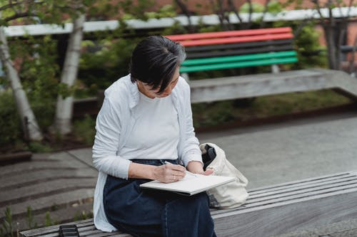 Woman in White Long Sleeve Shirt and Blue Denim Jeans Sitting on Bench Reading Book