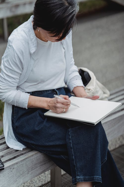 Woman in White Long Sleeve Shirt and Blue Denim Jeans Sitting on Gray Concrete Bench