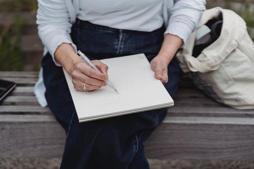 Person in Blue Denim Jeans and White Long Sleeve Shirt Holding Pen and White Paper