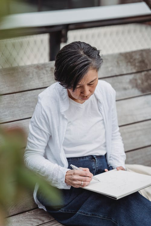 Woman in White Long Sleeve Shirt and Blue Denim Jeans Sitting on Brown Wooden Bench