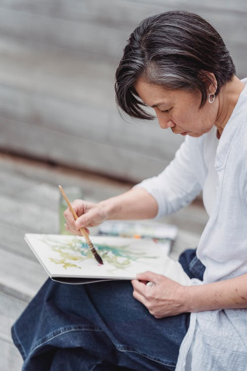 Woman in White Long Sleeve Shirt Painting