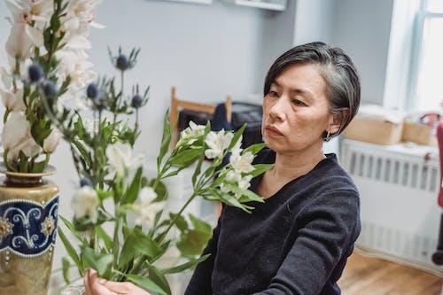 Woman in Black Long Sleeve Shirt Holding White Flower