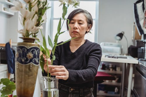 Woman in Gray Sweater Holding Green Plant
