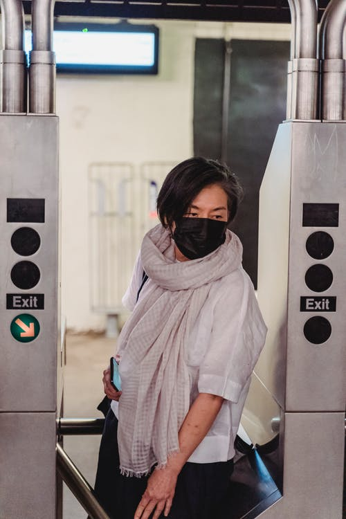 A Woman Passes Through a Turnstile at a Train Station