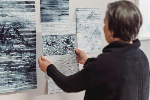 Mulher De Casaco De Lã Preto Olhando Para Uma Pintura Abstrata