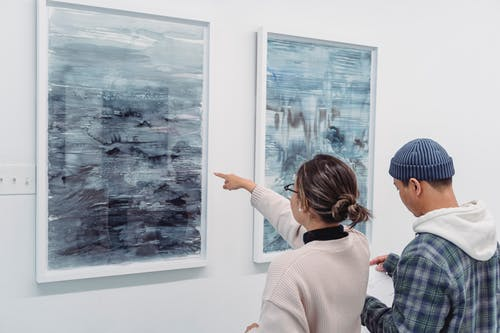 Man and Woman Standing near the Abstract Paintings Hanged on the Wall