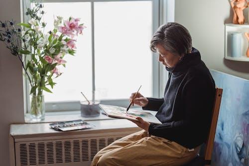 Una Mujer Pintando Una Obra De Arte En Un Bloc De Dibujo