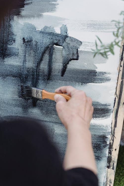 Person Holding Black and Orange Paint Brush