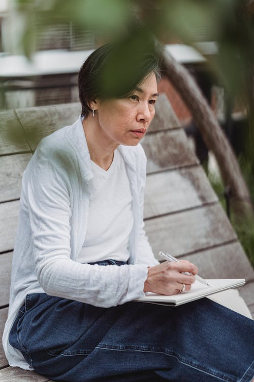 Woman in White Long Sleeve Shirt and Blue Denim Jeans Sitting on Gray Wooden Bench