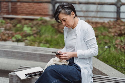 Woman in White Long Sleeve Shirt and Blue Denim Jeans Sitting on Gray Wooden Bench during