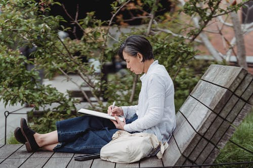 Woman in White Long Sleeve Shirt Reading Book Sitting on Gray Wooden Bench