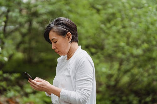 Woman in White Long Sleeve Shirt Holding Black Smartphone
